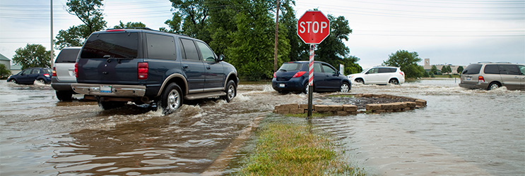 An SUV drives through a flooded roadway