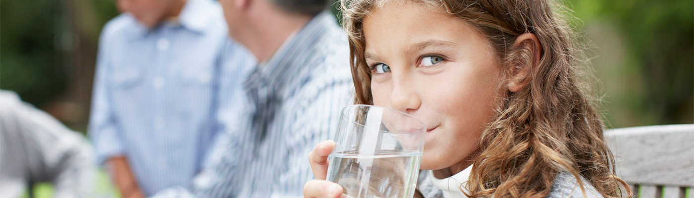 Young girl sipping a glass of water