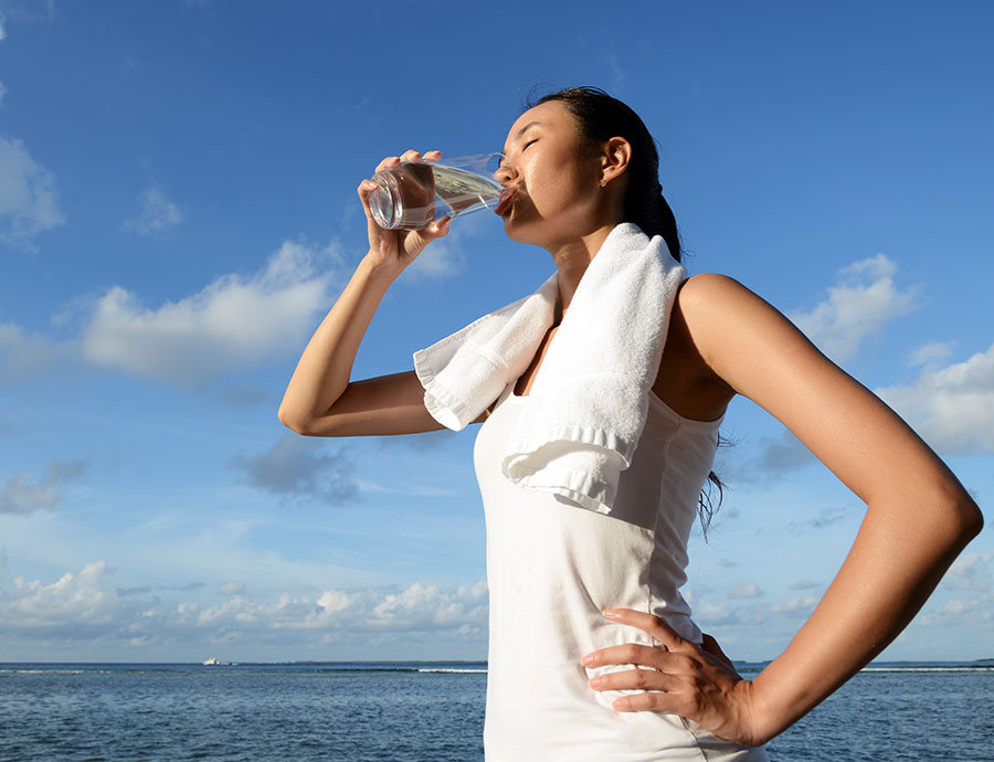 Woman taking a big drink of water after working out