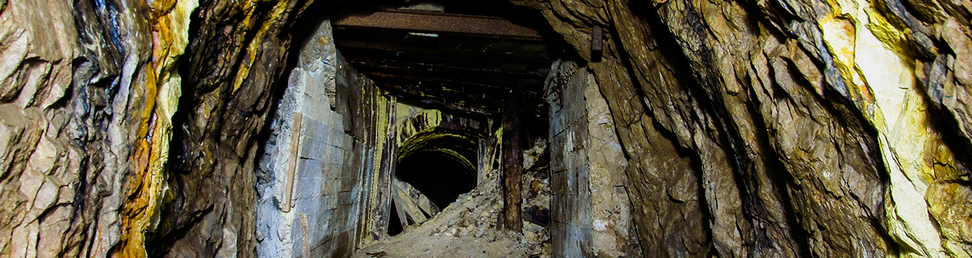 Abandonded mine with a blocked entrance and yellow stains