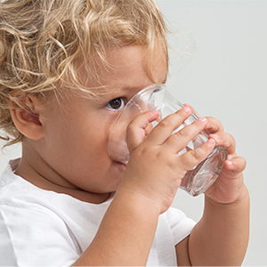 Toddler taking a big drink of water from a glass