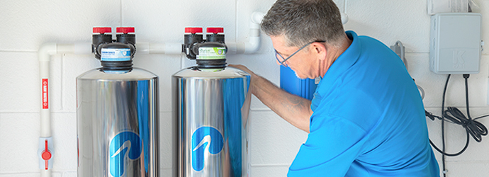 Company service technician cleaning a home filtration tank