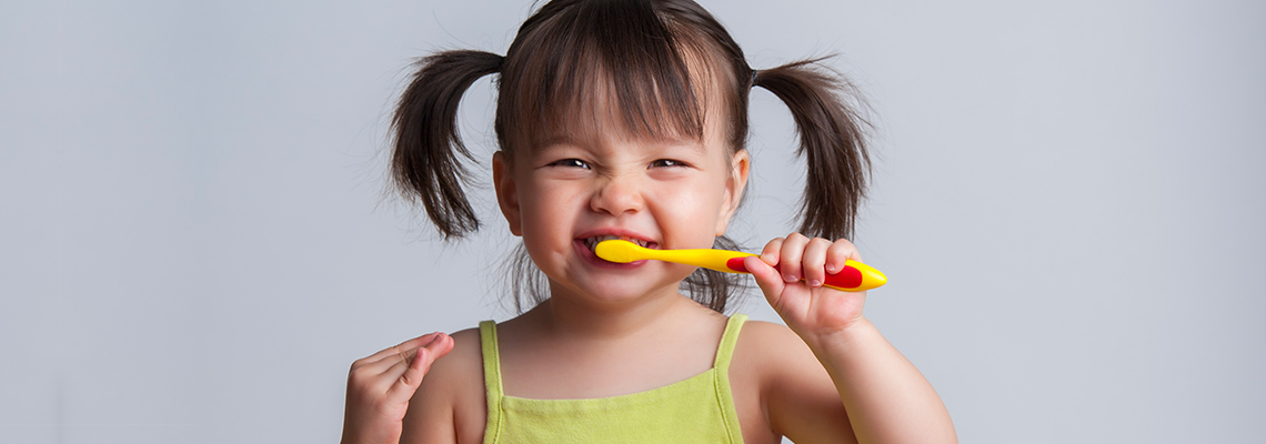 Toddler brushing her teeth with a smile