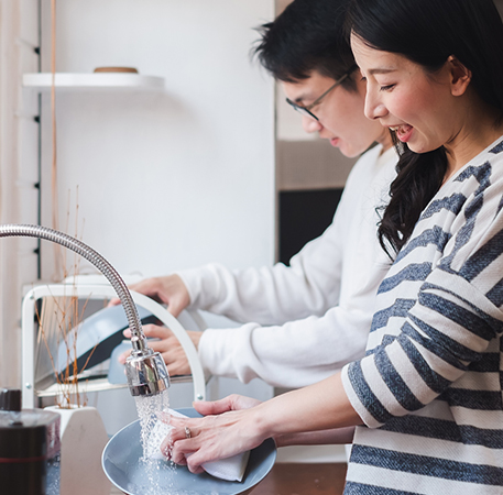 A young couple wash dishes together while chatting